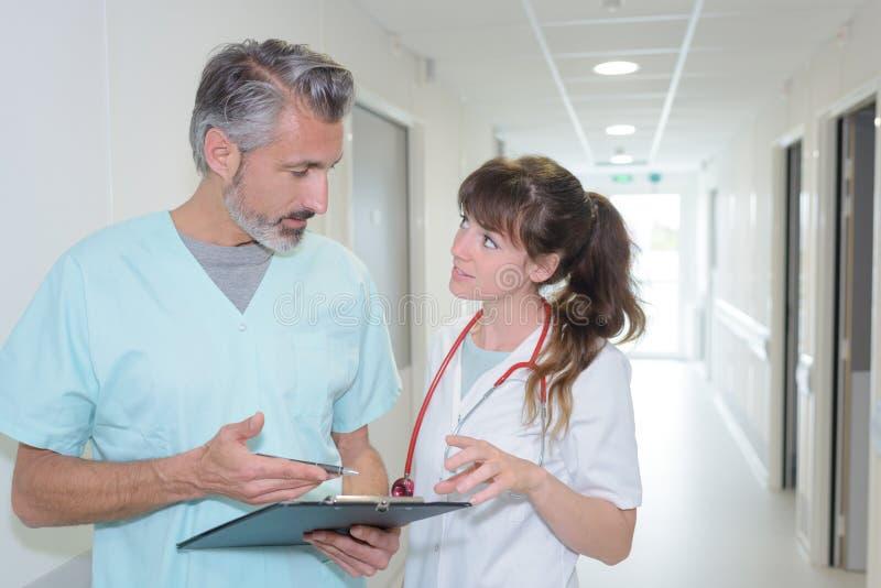 医护人员谈论笔记在医院走廊 免版税库存图片
