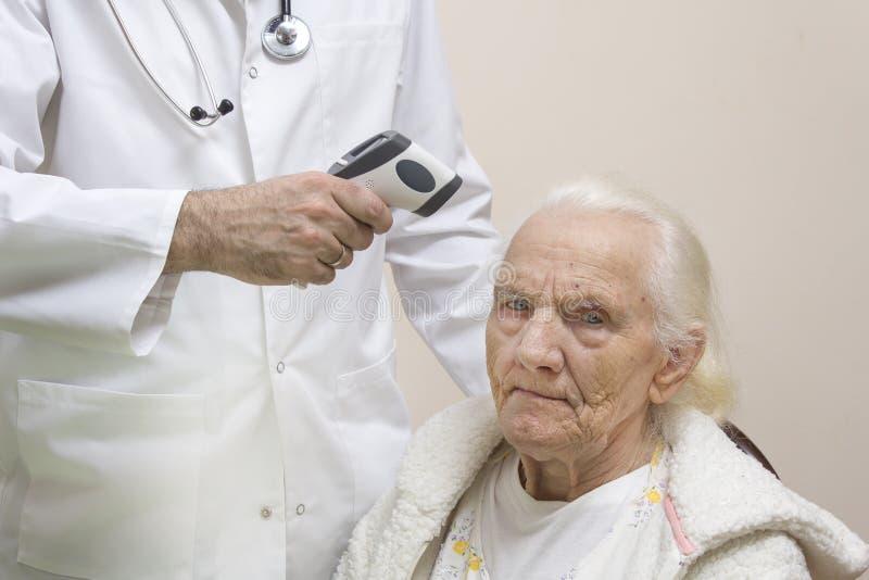 医治在一件白色外套测量与一名非常老灰色妇女的激光温度计的温度 库存图片