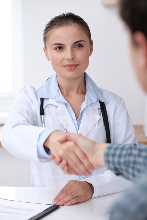 医治微笑的妇女,当与她的男性患者握手时 医学和信任概念 图库摄影