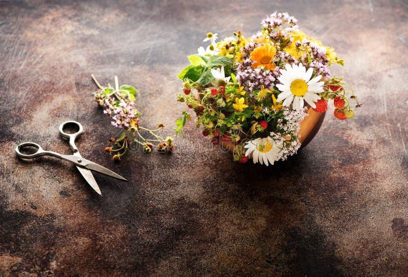 医治草本和花在一个木碗做的清凉茶和剪刀 免版税库存照片