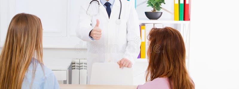 医生与妇女患者谈话并且在医疗办公室坐 免版税库存照片