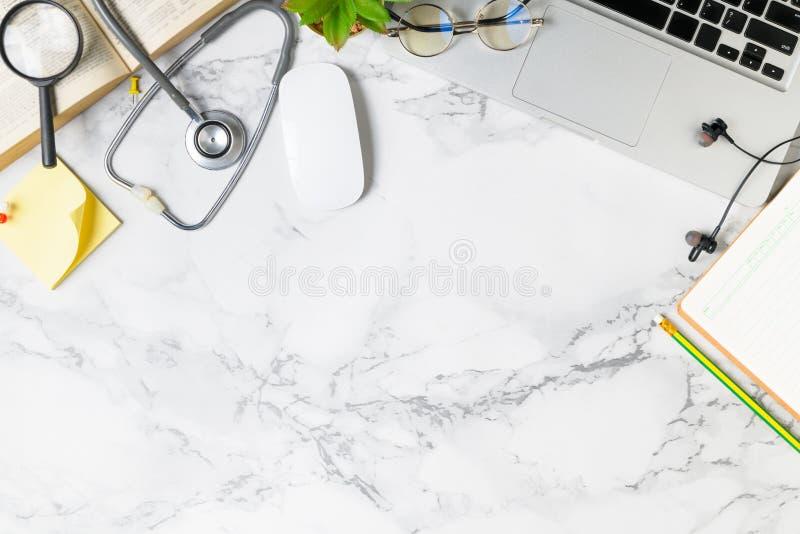 医生书桌与听诊器的大理石桌顶视图  库存图片