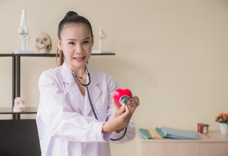 医生亚裔妇女递显示被弄脏的仪器心脏红色模型,愉快和微笑,选择聚焦 库存照片