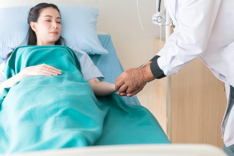 医生人手用对耐心亚裔妇女的食盐水和在医院的继续采取的行动治疗 库存图片