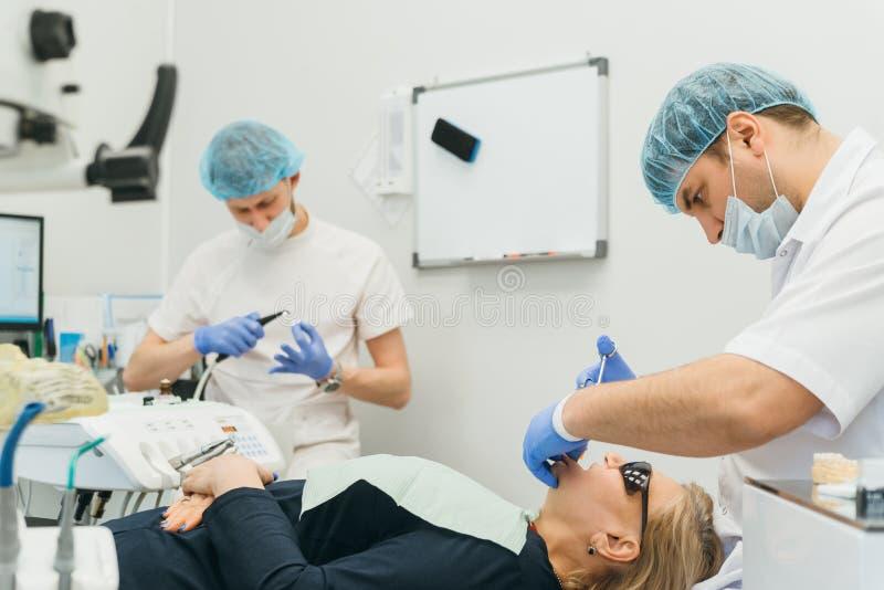 医生使用的显微镜 牙医在现代牙齿办公室治疗患者 使用浮桥坞,操作进行 免版税库存图片