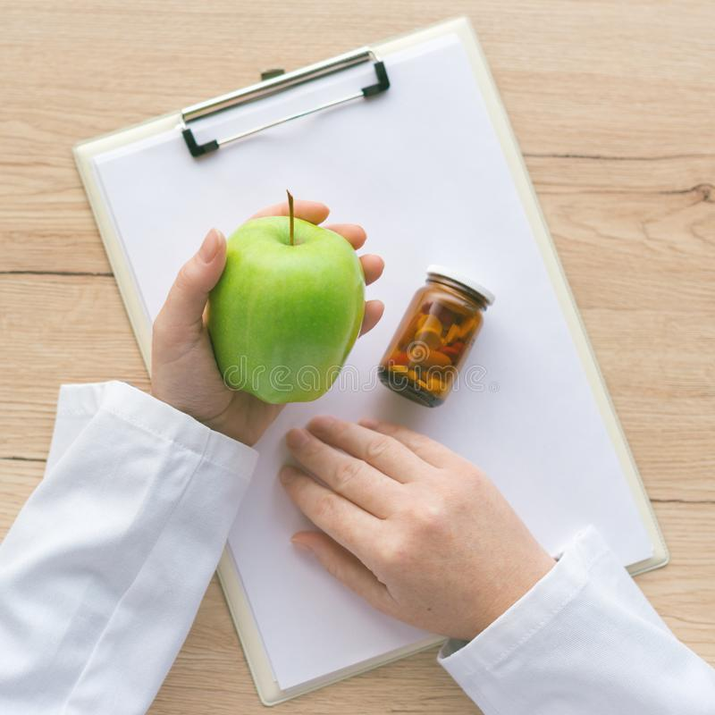 医生劝告苹果而不是药片和抗生素 库存图片