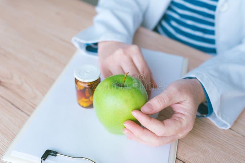 医生劝告苹果而不是药片和抗生素 库存照片
