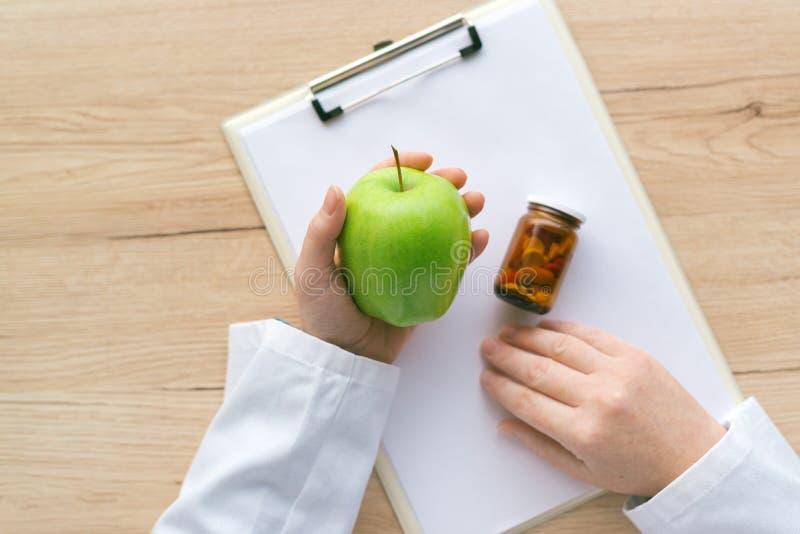 医生劝告苹果而不是药片和抗生素 图库摄影