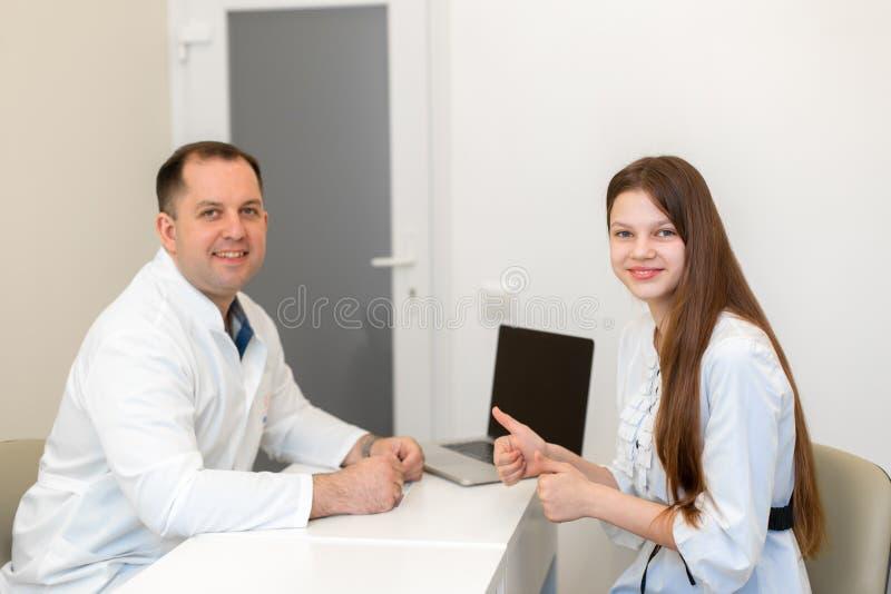 医生劝告诊所的一个少年女孩 库存照片
