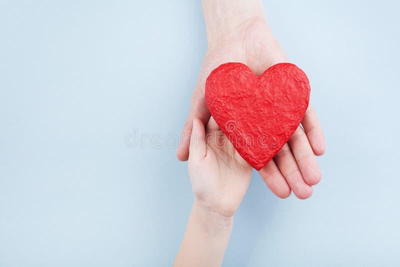 医生和孩子在手上的拿着红色心脏 家庭关系,医疗保健,小儿科心脏病学概念 免版税库存照片