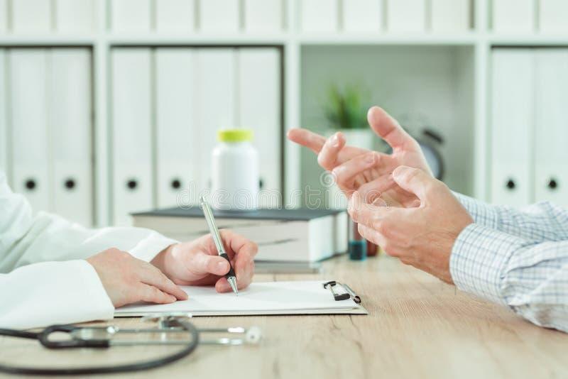 医生和患者在咨询时在医疗办公室 免版税图库摄影