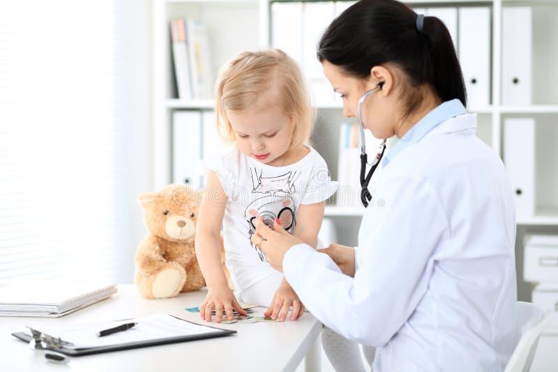 医生和患者婴孩在医院 小女孩由有听诊器的儿科医生审查 胳膊关心健康查出滞后 免版税库存图片