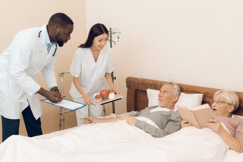 医生和护士为床提供一对年长夫妇一个苹果、蛋白软糖和松饼 库存照片