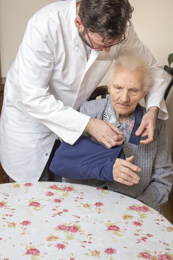 医生和护士帮助老妇人从椅子起来 一个老妇人用在吊索的一只手 库存照片