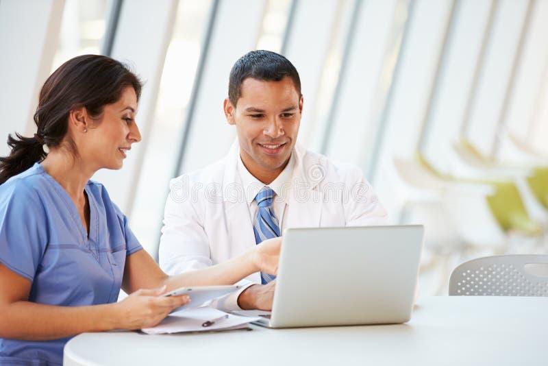医生和护士开非正式会议在医院军用餐具 免版税库存图片