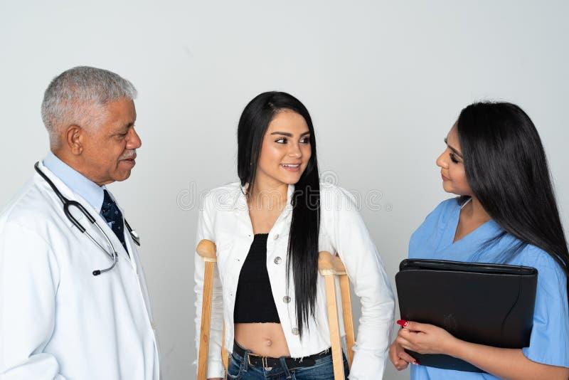 医生和护士有患者的白色背景的 免版税库存照片
