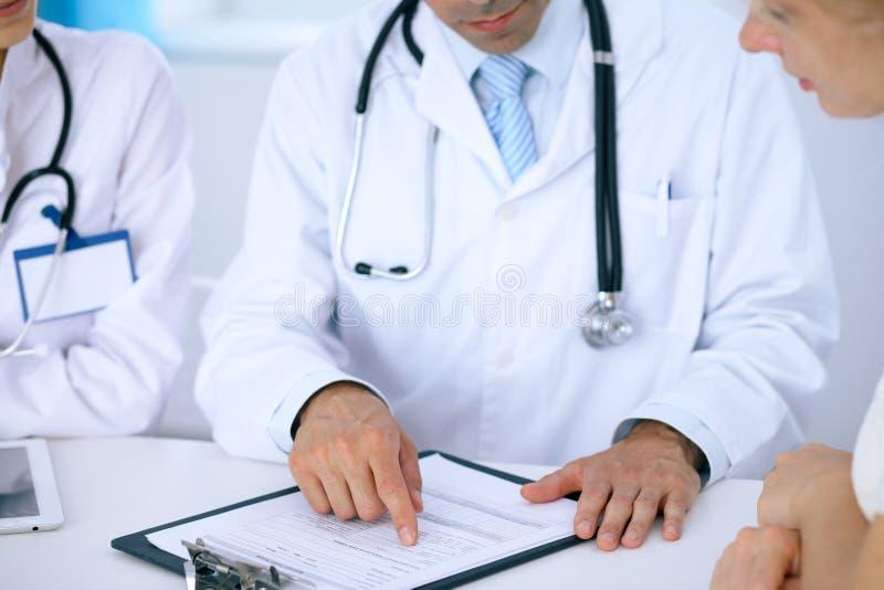 医生和耐心谈话,当坐在书桌在办公室时 指向入病史形式的医师 Medicin 图库摄影