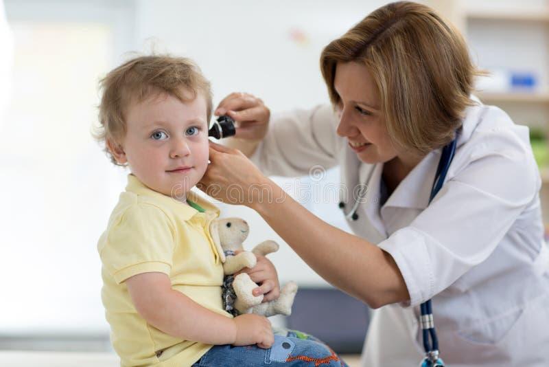 医生在儿科医生屋子审查有耳镜的耳朵 医疗设备 免版税图库摄影