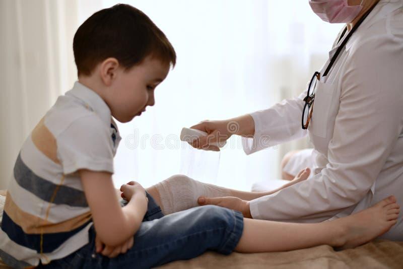 医生在孩子上把医疗绷带放 库存图片