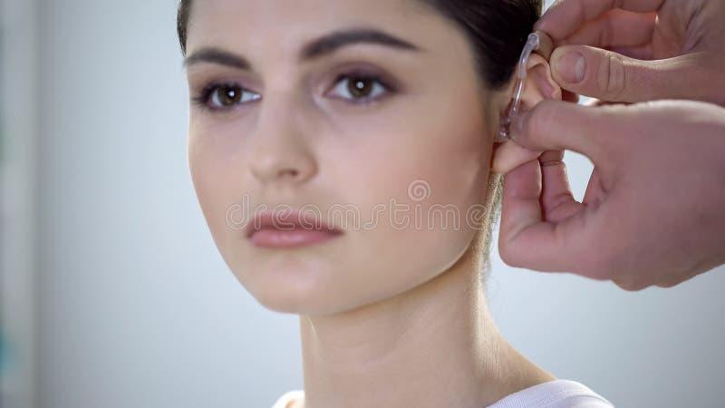 医生在小姐耳朵,听力损伤,残疾的工作上把聋援助放 免版税库存图片