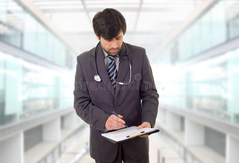 医生在想。男医生在医院用笔记思考 免版税库存照片
