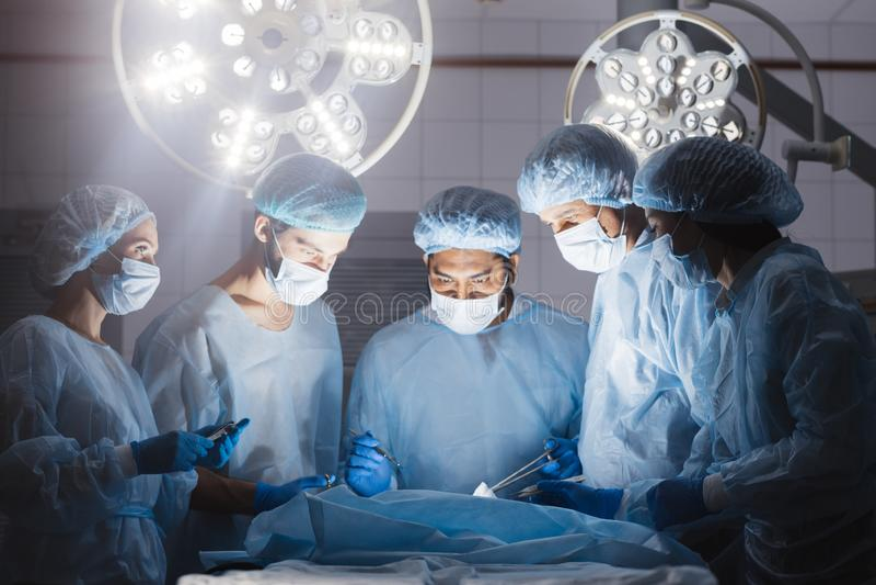 医生在手术在黑暗的背景中合作 库存图片