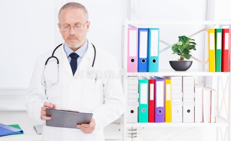医生在文件夹写某事在诊所办公室 免版税库存图片