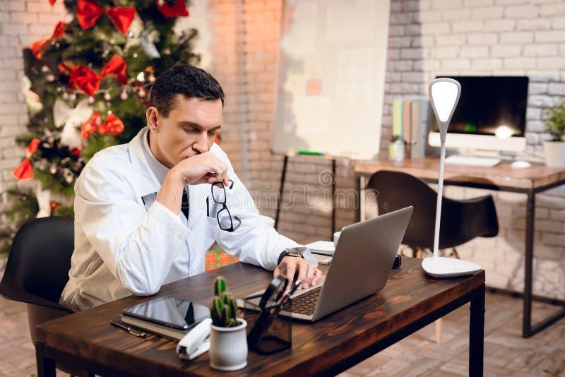 医生在新年` s伊芙工作 他` s在办公室和他s乏味的` 库存照片
