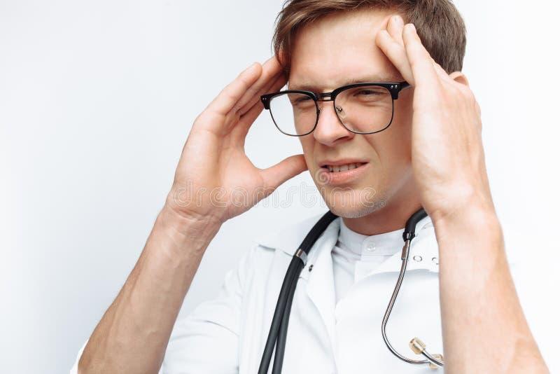 医生在白色背景犯了一个错误,一名年轻学生的遗憾, 免版税图库摄影