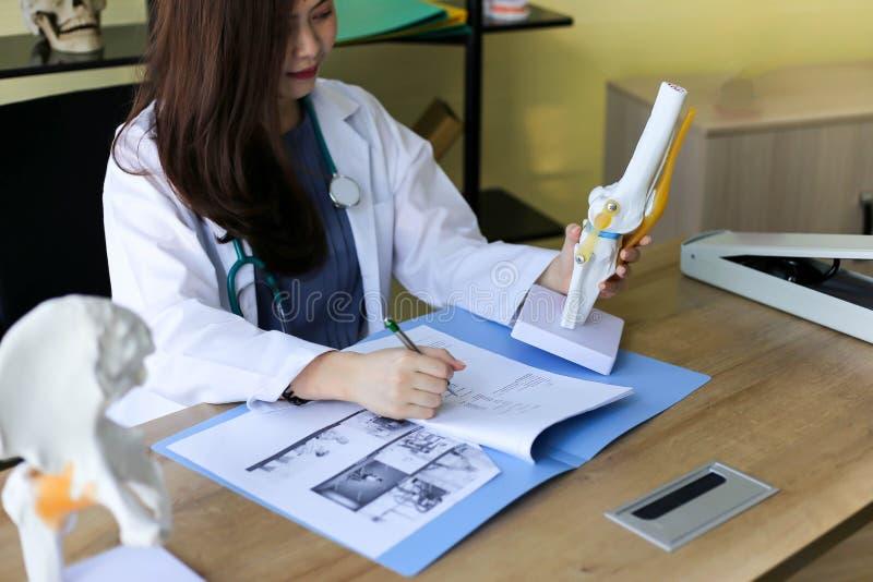 医生在脊椎的一根骨头指向膝盖的布局 免版税库存图片