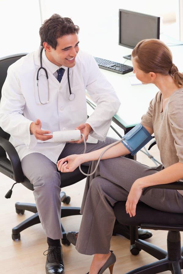 医生在采取他的患者血压以后被解除 库存图片