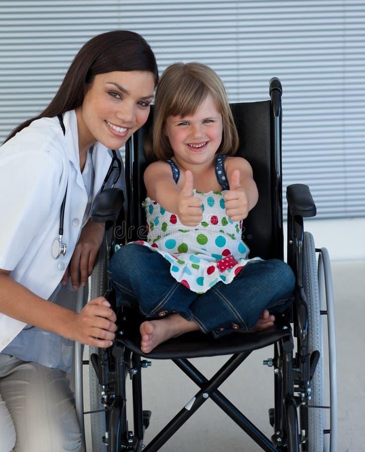 医生女孩她小的轮椅 免版税库存照片
