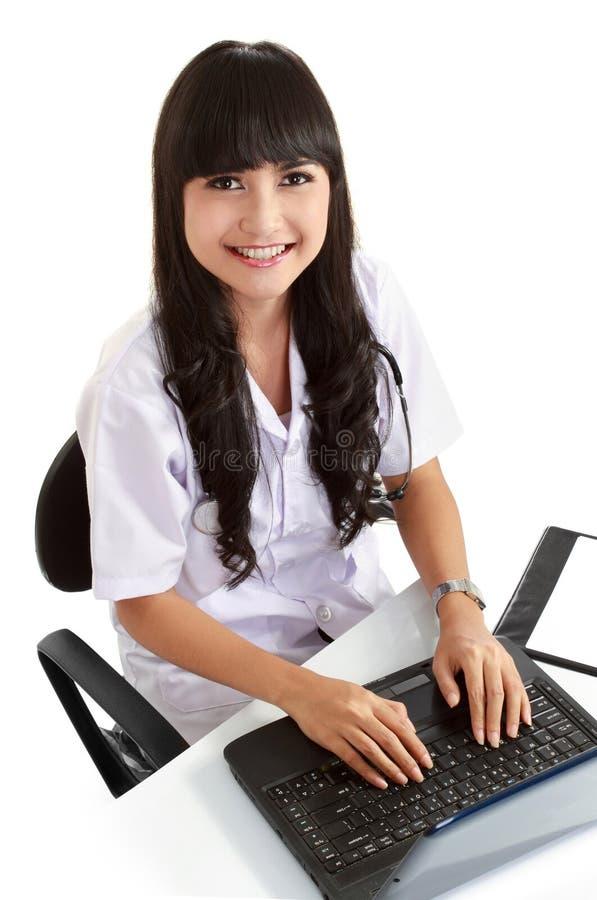 医生女性她的膝上型计算机工作 免版税图库摄影
