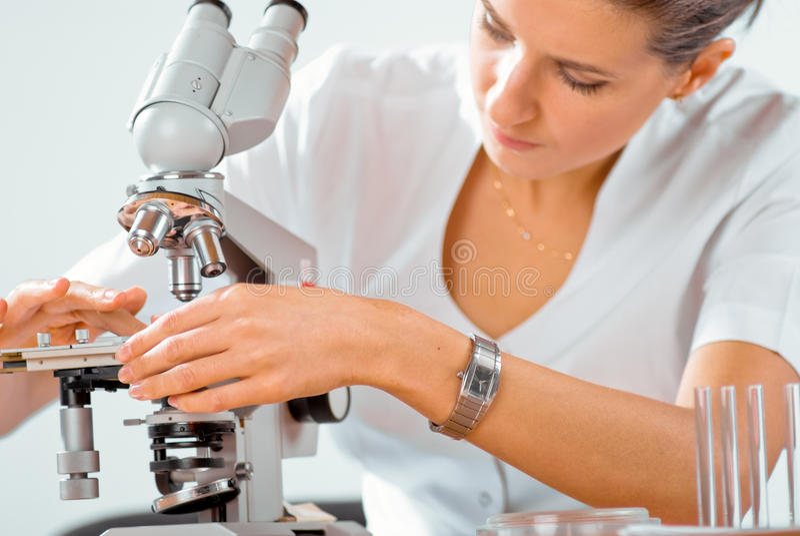 医生女性显微镜工作 免版税图库摄影