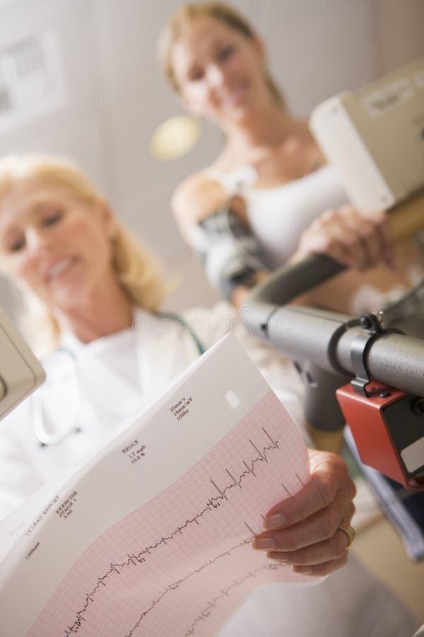 医生女性监控患者踏车 免版税库存图片