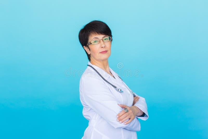 医生妇女与听诊器的微笑面孔在蓝色背景 免版税库存图片