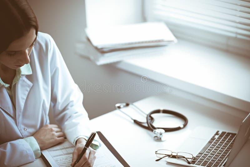 医生妇女与药物史纪录一起使用在医院时形成,当坐在书桌靠近窗口 ?? 免版税库存照片
