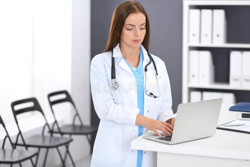医生妇女在工作 使用便携式计算机的女性医师画象,当站立近的总台在诊所或时 库存照片