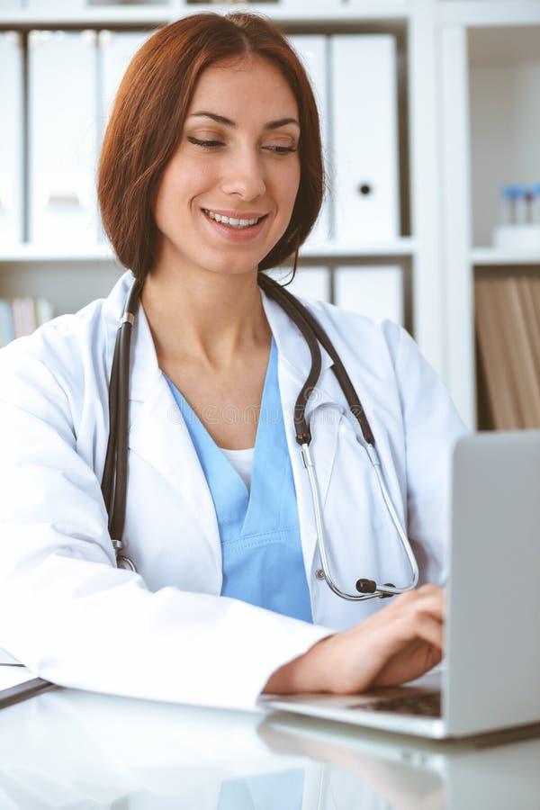 医生妇女在工作 键入在手提电脑的医师 o 库存照片