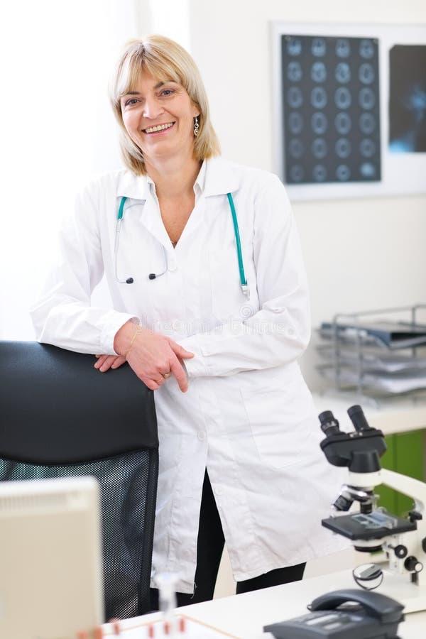 医生实验室纵向高级微笑的妇女 免版税库存图片