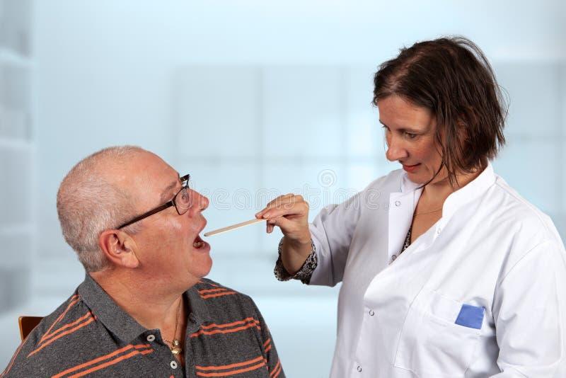 医生审查有舌头小铲的喉头 免版税库存照片