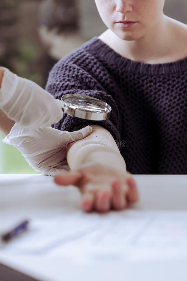 医生审查的癌症痛苦患者在医疗中心 免版税库存图片