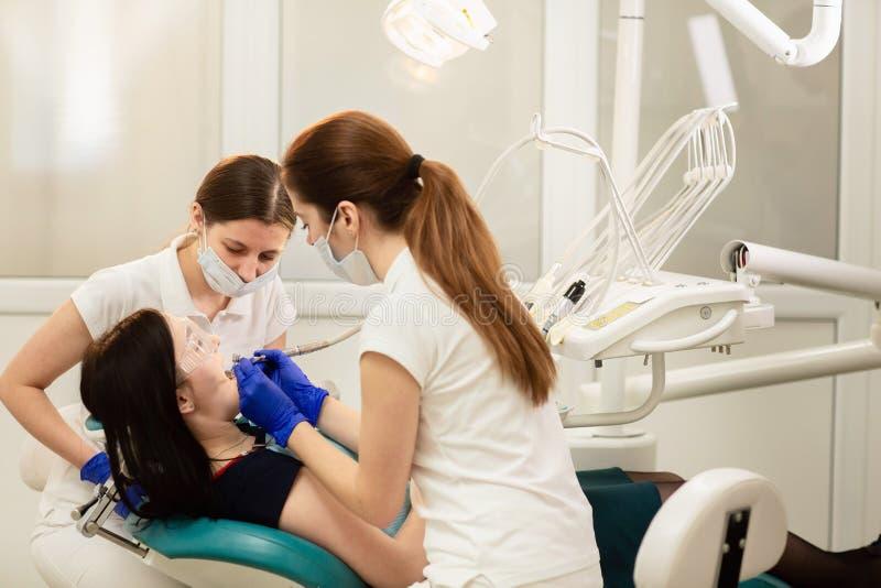医生对待患者的牙的丝毫助理,防止龋 口腔医学概念 图库摄影