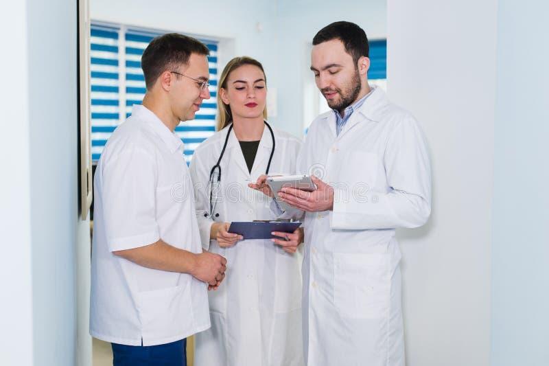医生工作在医院和谈论在医疗报告 分析和运转在诊所的医护人员 免版税库存图片
