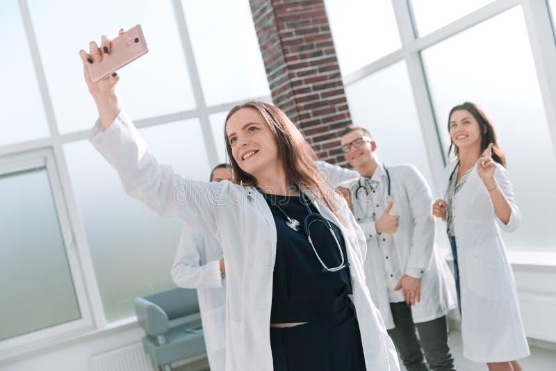 医生微笑的队在采取selfie的医疗中心 免版税库存照片