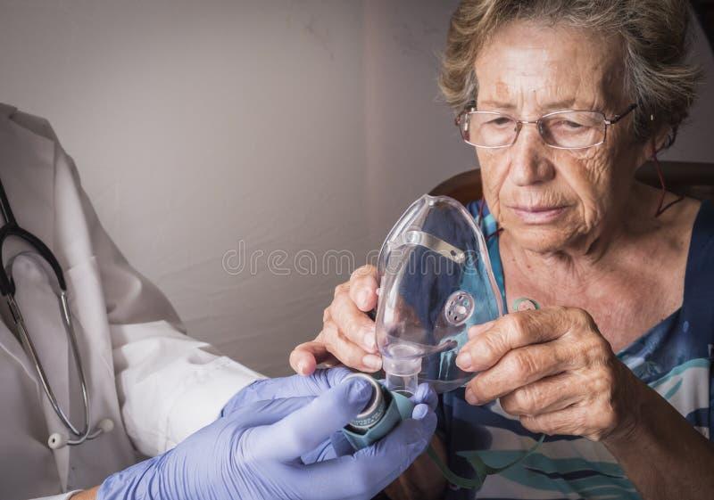 医生怎么解释给老妇人ventimask吸入治导工程 免版税库存照片