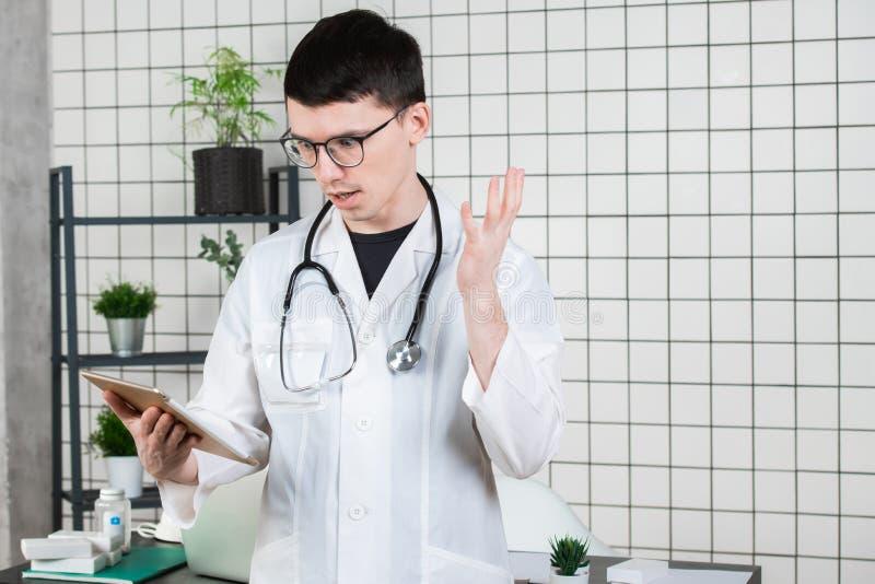 医生惊奇,冲击从关于片剂的笔记 免版税库存照片