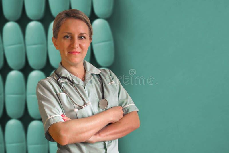 医生或护士制服的有听诊器的在脖子和横渡的手上 愉快的正面微笑白人妇女 在深蓝药物 免版税图库摄影