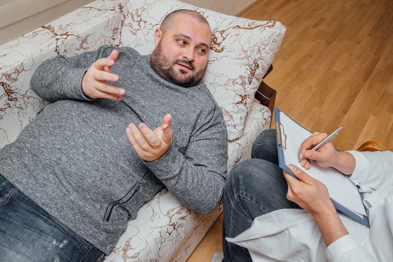 医生拜访他的患者 病的哀伤的人谈话与关于他的问题的医生 医生写笔记 免版税库存图片