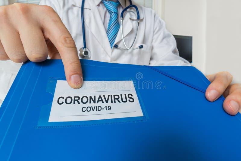 医生拿着蓝色文件夹,冠状病毒COVID-19诊断 免版税库存照片